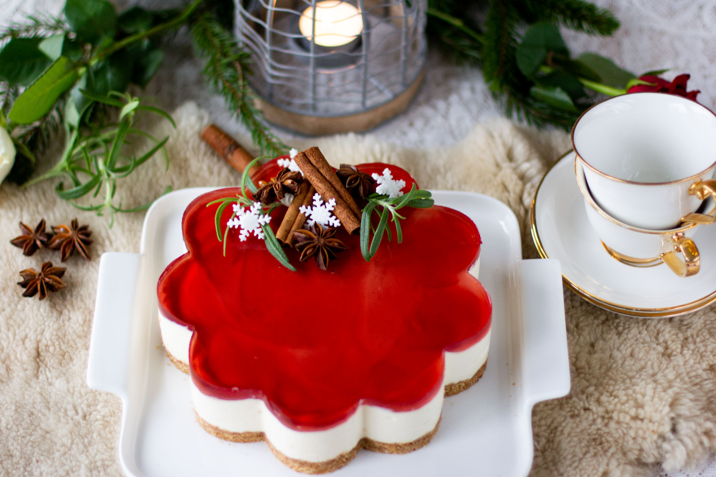 Herkullinen glögijuustokakku amarettotäytteellä ja punaisella glögikiilteellä.
