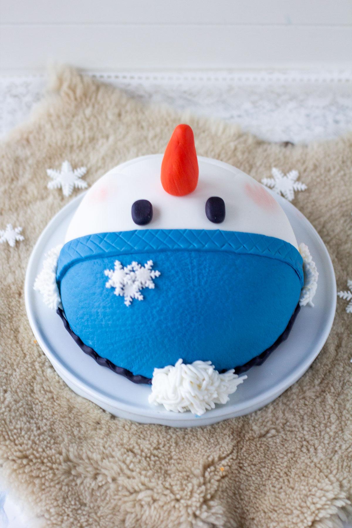 Valmis lumiukkokakku väärinpäin. Näkyy sokerimassan kuviointi
