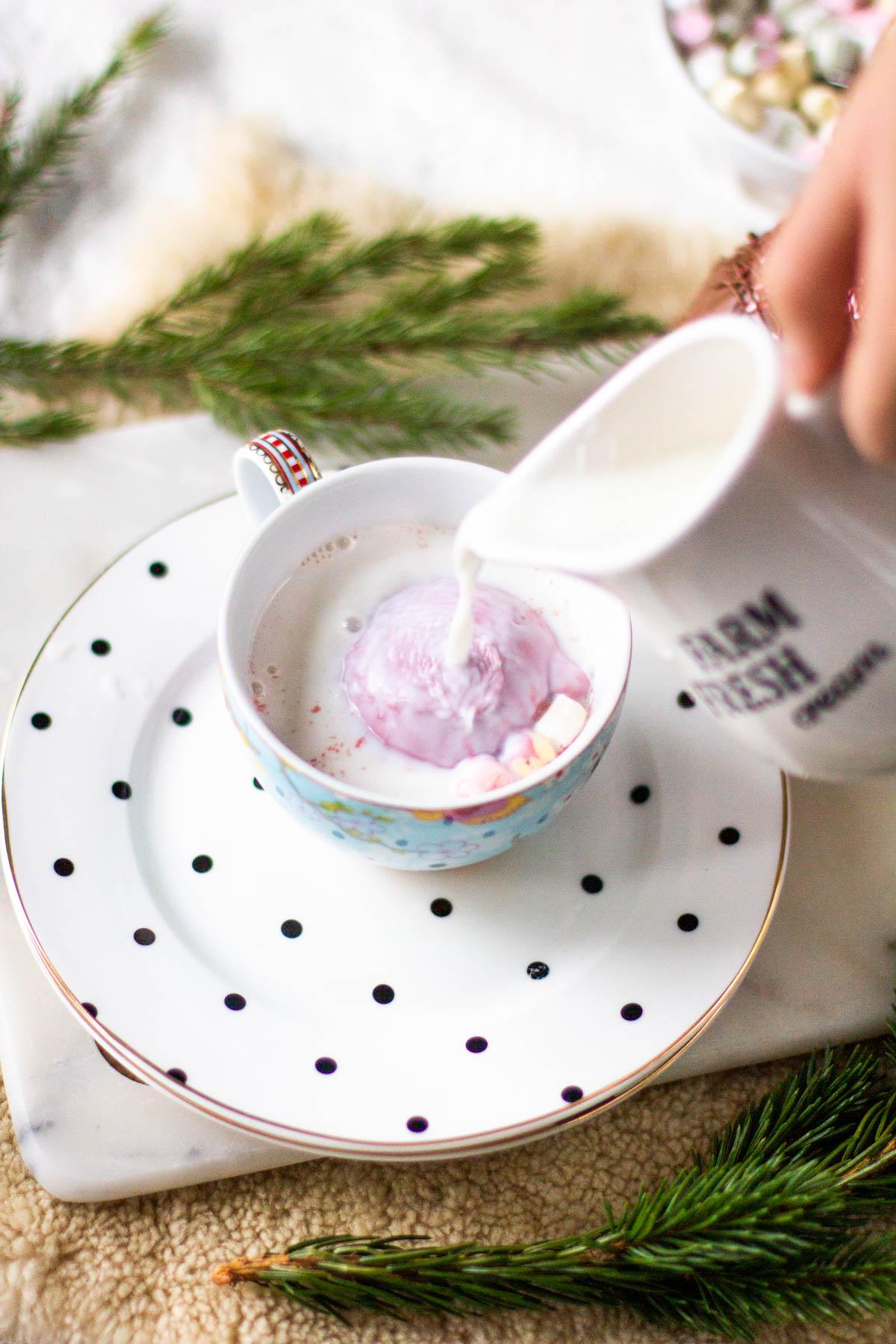 Maidon kaataminen kaakaopallon päälle ja sisältä vapautuvat vaahtokarkit